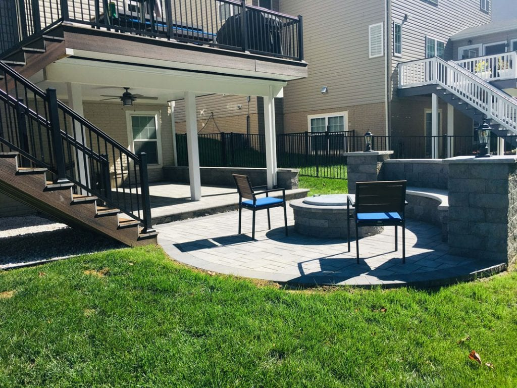 custom patio with seat wall and fire pit - adjacent to new deck