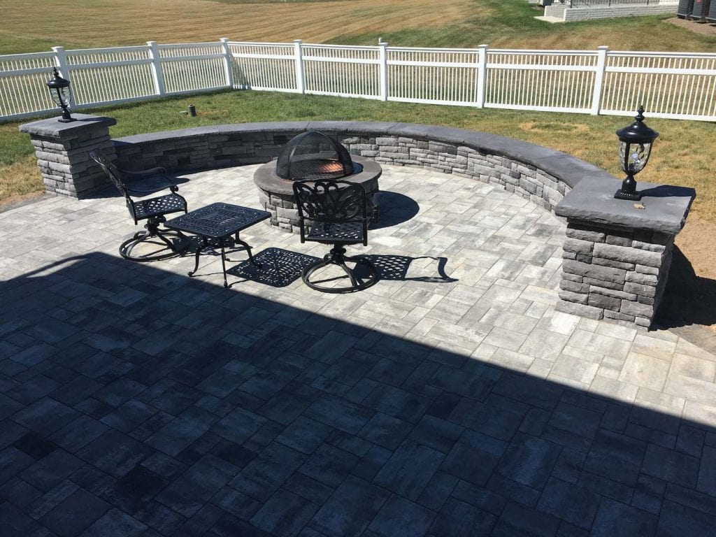 Gray patio with wall with black capstone and landscape lighting