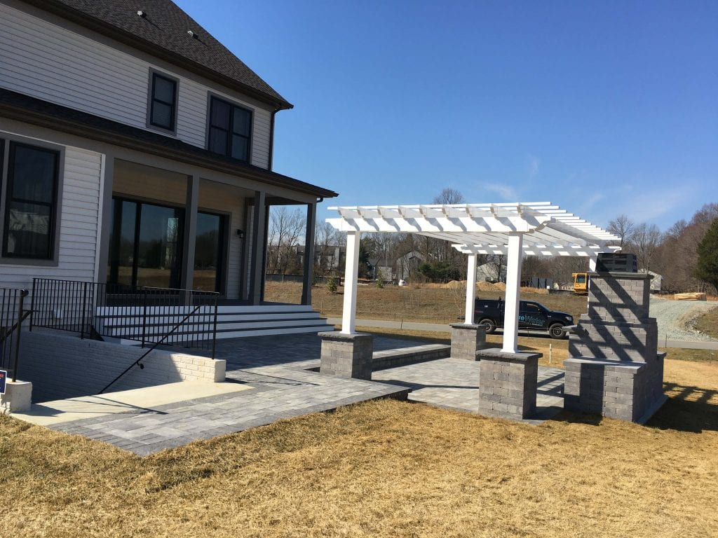 Gray paver patio with pergola and fireplace