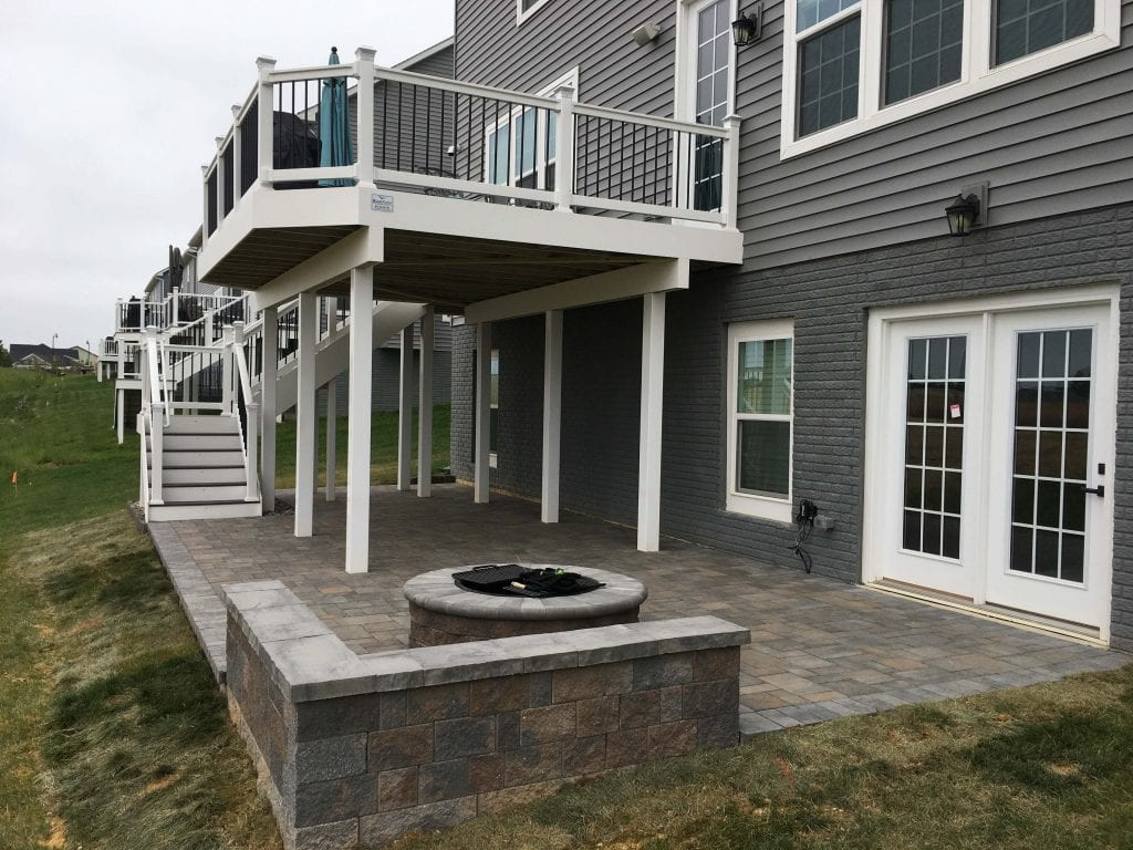 View of gray and brown stone patio with fire pit and composite deck