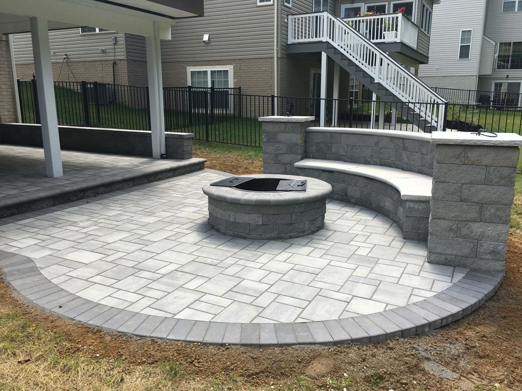 custom patio with seat wall and fire pit - gray natural stone pavers