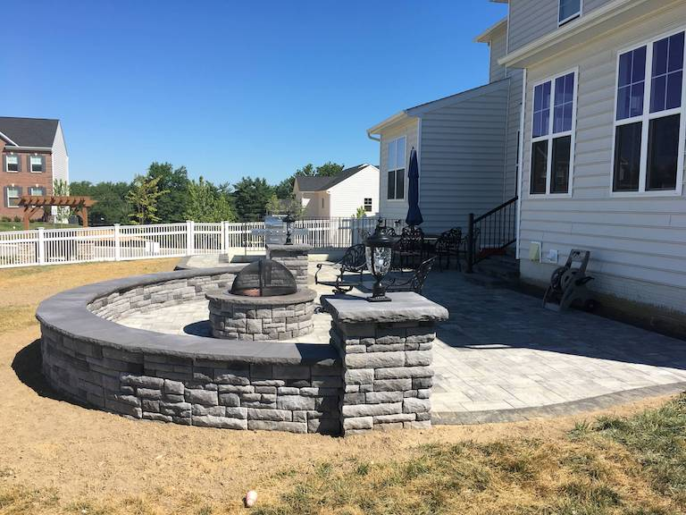 fire pit and patio with seat wall with exterior lighting built in