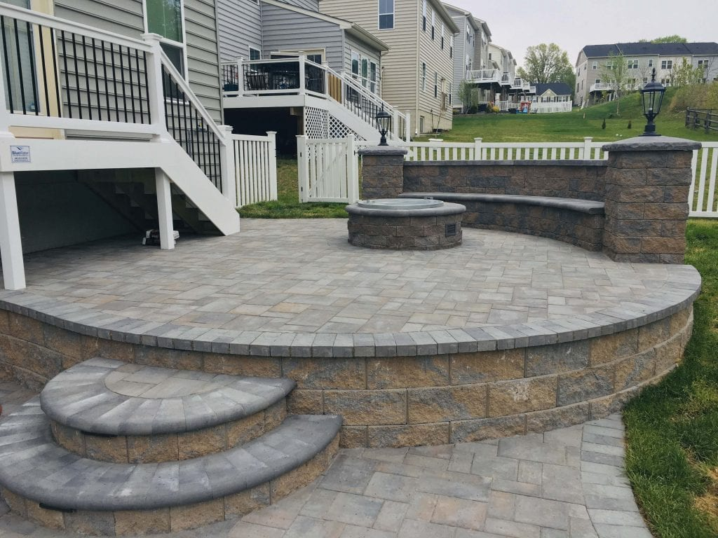 Gray and brown paver patio with fire pit and seat wall of natural stone