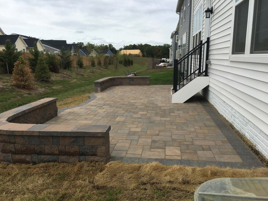 new Construction - back yard paver patio with wall and black edge