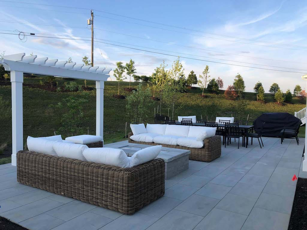 outdoor living project - natural stone patio with pergola and outdoor sofas and dining