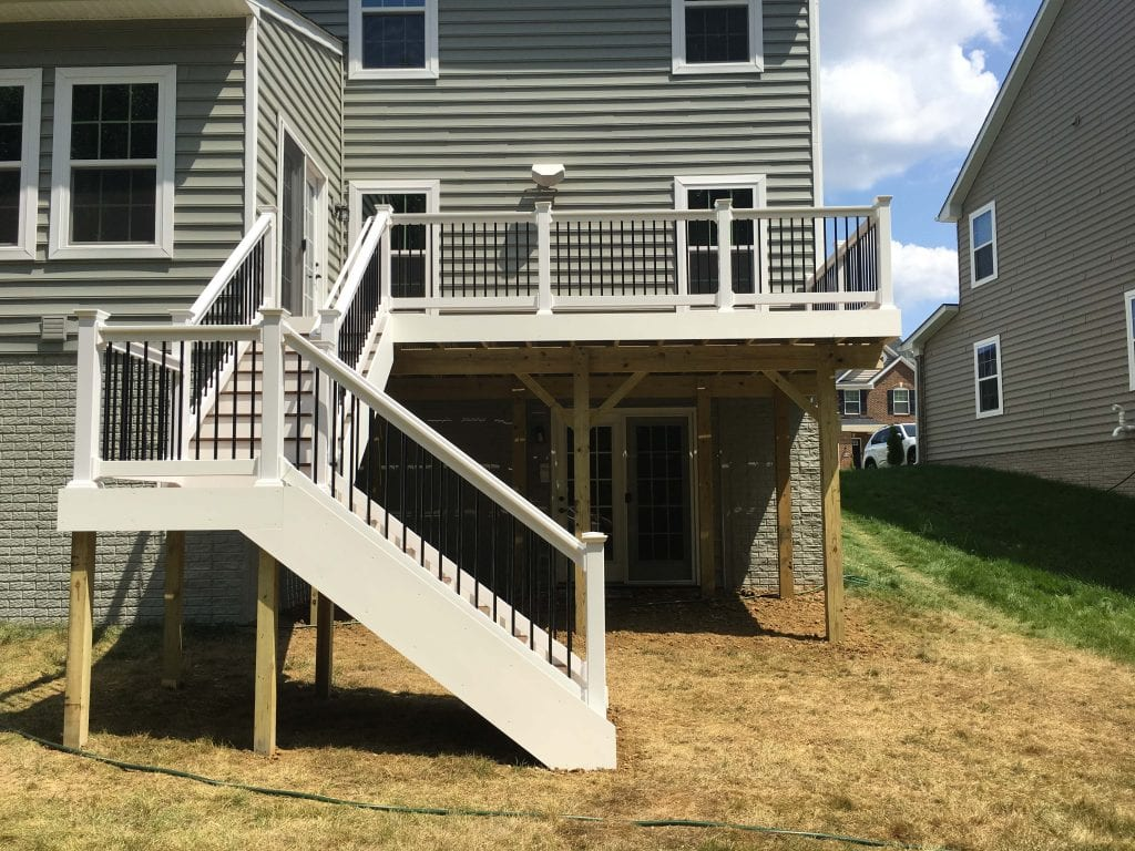 Two story White composite wood deck installed on rear of home