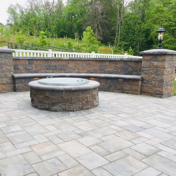 fire pit with seat wall and custom landscape lighting built in