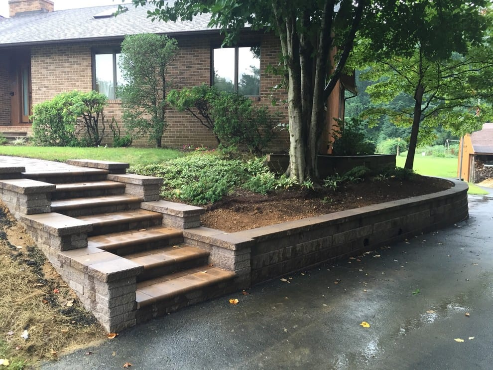 natural stone stairway and sidewalk along retaining wall adjacent to driveway