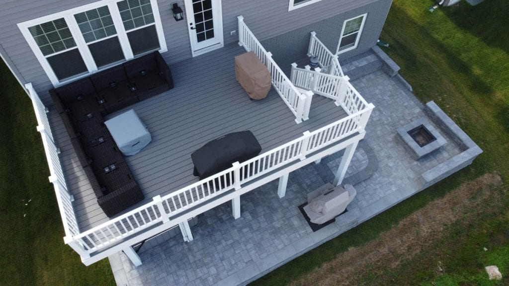 Aerial view of new deck construction, new paver patio, and new fire pit