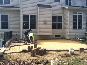 Placing pavers during patio construction at home