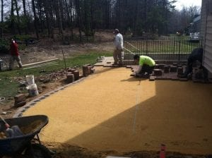 Placing pavers during patio construction behind home