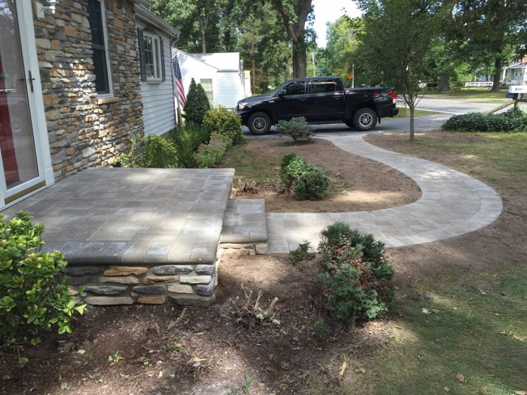 Serpentine paver sidewalk leading to front stoop in the front of house