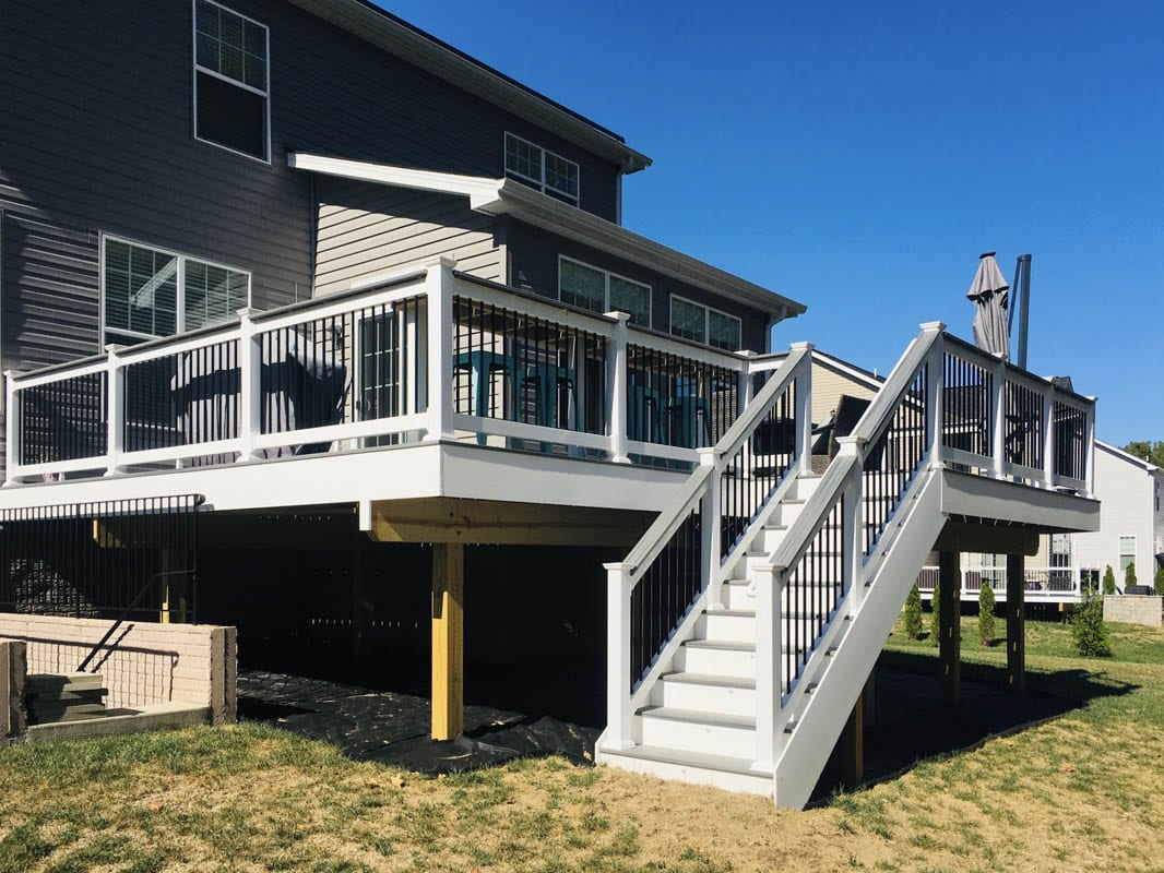 Newly built white composite deck with stairway on rear of home