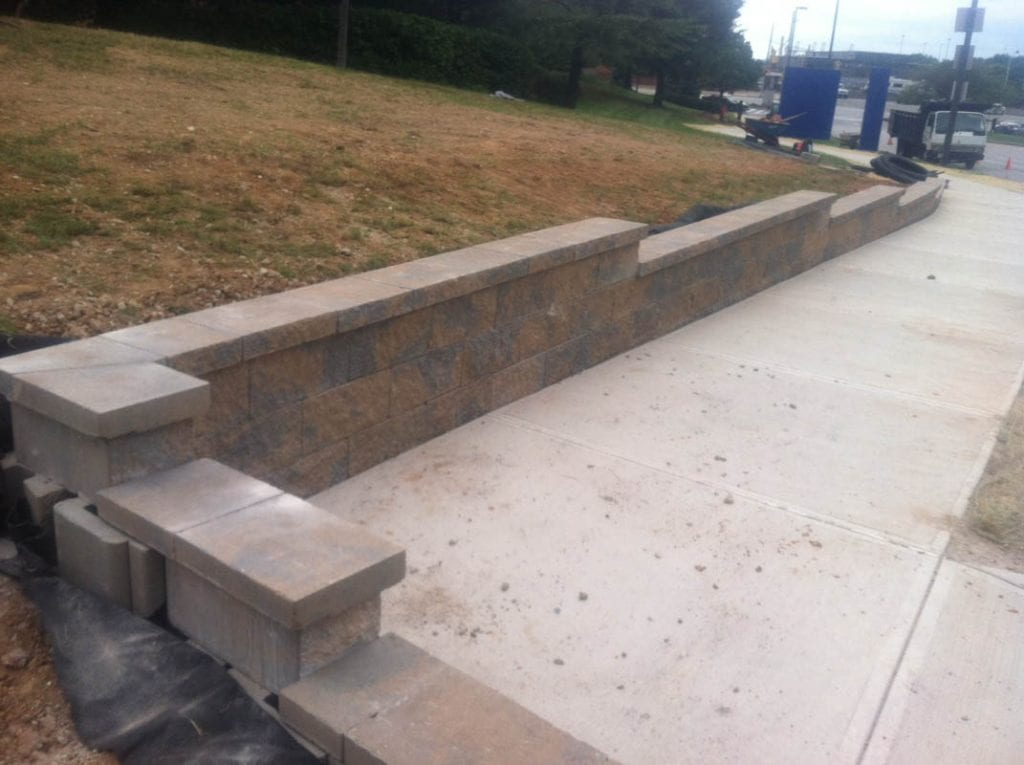 Retaining wall built along a sidewalk adjacent to a slope