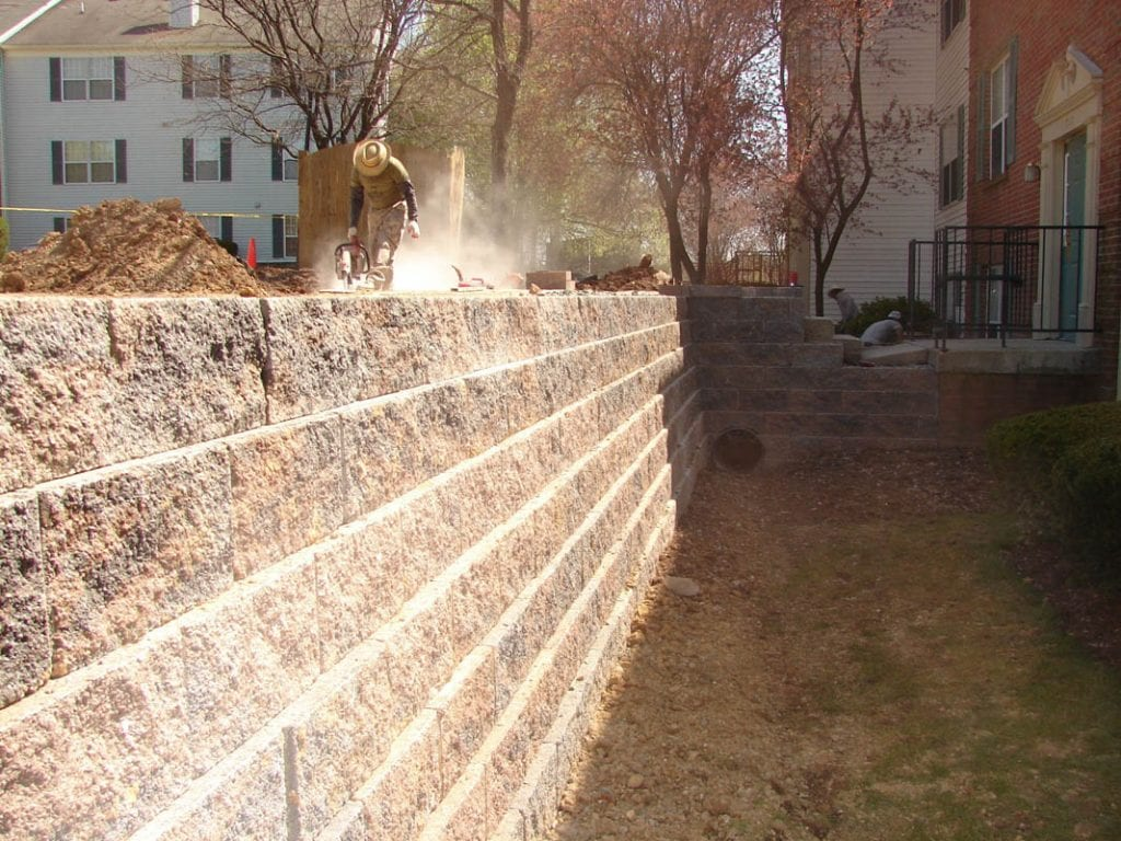 Retaining wall being constructed adjacent to a home