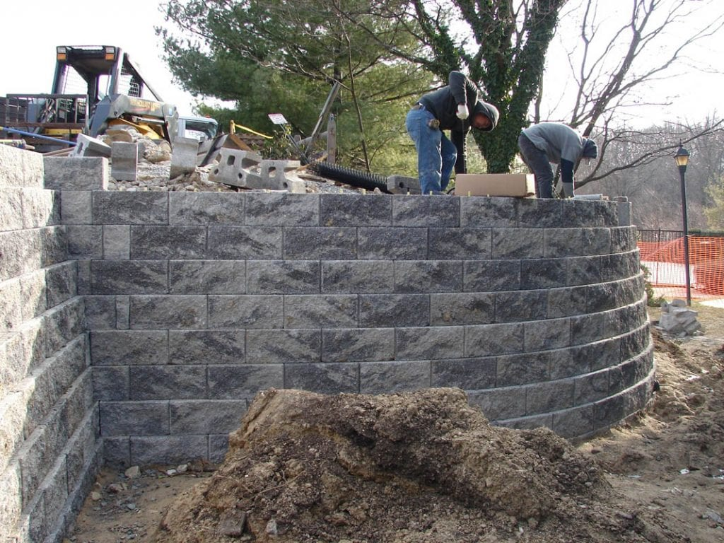 Placing blocks for construction of a stone retaining wall