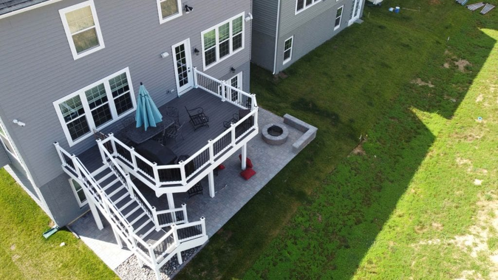 Aerial view of composite deck with paver patio and fire pit beneath
