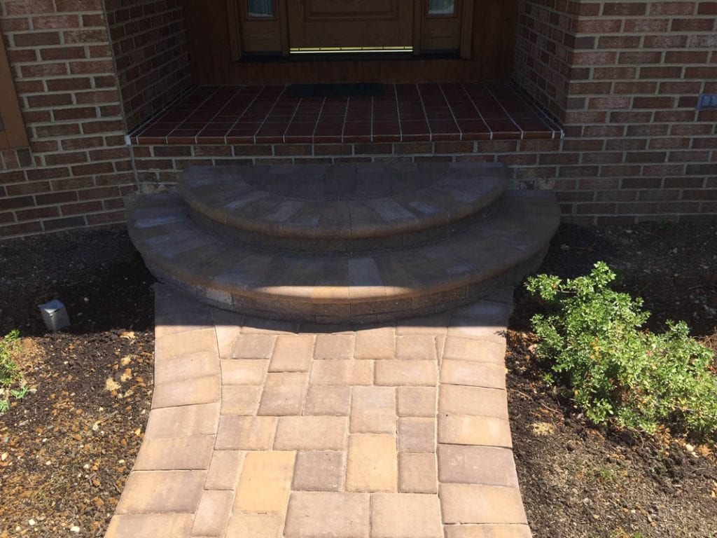 Brown paver walkway and stairs leading to front door