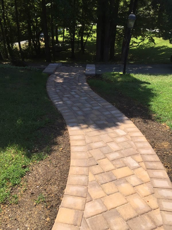 Serpentine S-shaped brown paver walkway leading from home to driveway