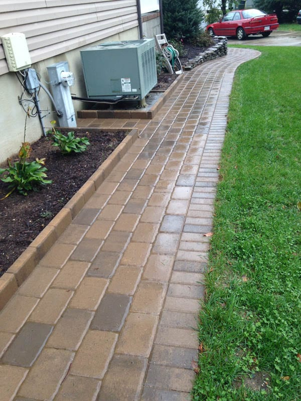 Natural stone paver sidewalk with glossy, wet-look finish running along home