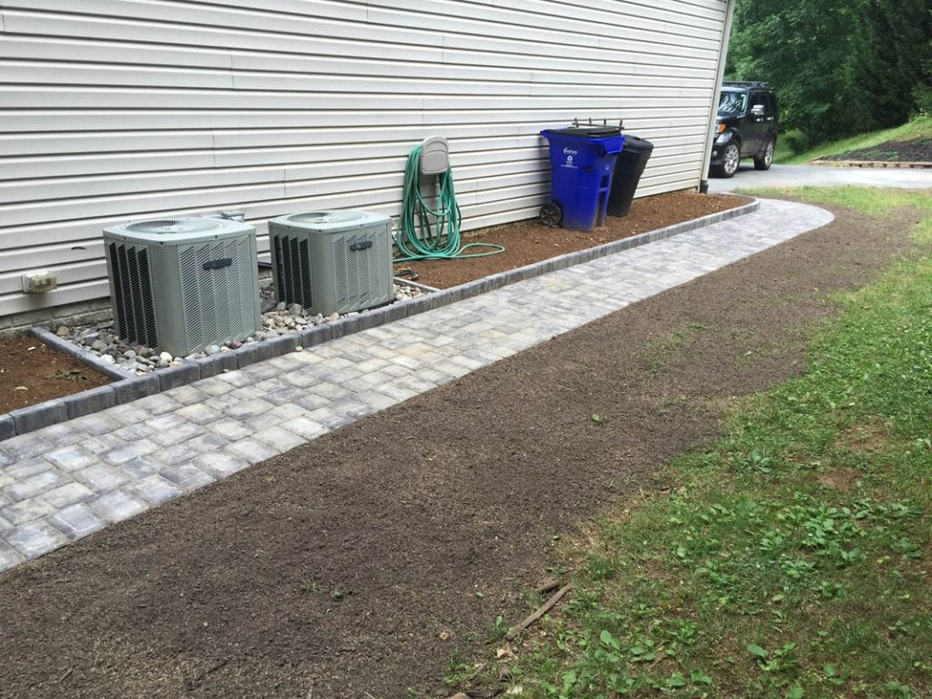 White and gray paver sidewalk running along the side of a house