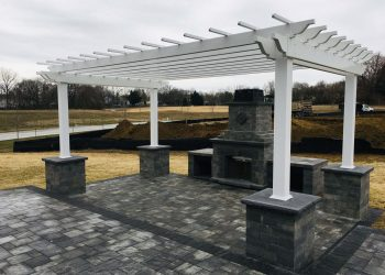 New outdoor fireplace and pergola with gray paver patio